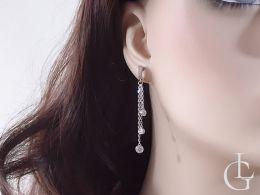 kolczyki srebrne wiszące z cyrkoniami na łańcuszku łańcuszek zdjęcie na modelce na uchu