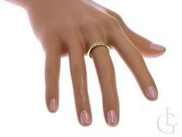 złota obrączka z cyrkoniami na palcu na dłoni