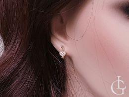 złote kolczyki wiszące serduszka na uchu