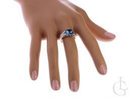 złoty ekskluzywny pierścionek z szafirem na palcu na ręce