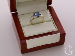 złoty ekskluzywny pierścionek z szafirem w pudełku