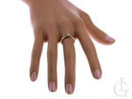 złoty klasyczny pierścionek zaręczynowy na dłoni na palcu jeden centralny kamień