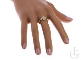 złoty pierścionek na palcu czterolistna koniczyna symbol szczęścia cyrkonie złoto żółte