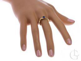 zmysłowy pierścionek złoty zaręczynowy na palcu złoto żółte szafir cyrkonie
