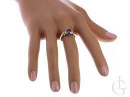 złoty pierścionek z fioletową cyrkonią pierścionek zaręczynowy na palcu na dłoni