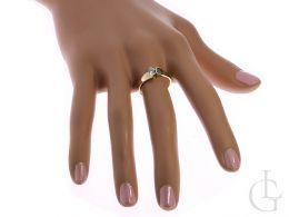 złoty pierścionek zaręczynowy na palcu na dłoni złoto żółte jeden centralny kamień