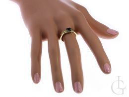 złoty pierścionek z szafirem na palcu na dłoni