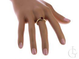 Złoty pierścionek z rubinem na placu na dłoni
