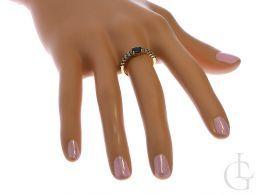 złoty pierścionek z szafirami na palcu